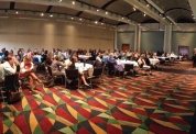 Prevention practitioners sit at tables at a state-wide conference