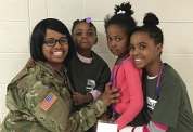 Mother in military uniform smiles with her three children.