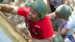 Prevention practitioner in helmet climbs wall during boot camp