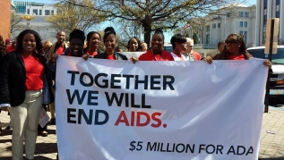 "Volunteers at HIV Awareness Day holding sign that says ""Together We Will End AIDS."""