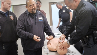 First responders practicing with naloxone on a dummy.
